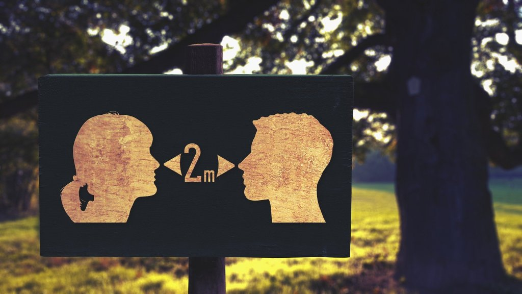 A sign showing a silhouette of a man and a woman with arrows stating to stay two metres apart